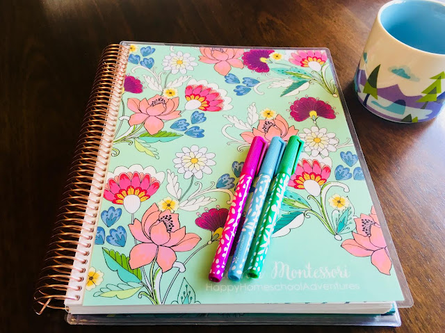 homeschool lesson planner, pens, and a coffee mug sitting on a table