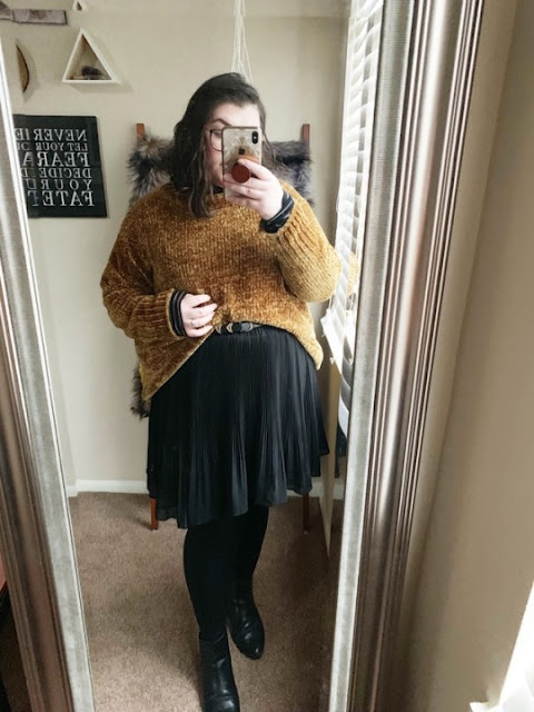 A mirror selfie of an outfit of mustard chenile sweater layered over a black and white striped turtleneck tucked into a black pleated chiffon mini skirt, with black tights and black booties.