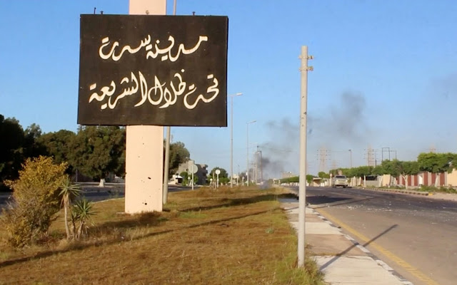 "Image Attribute: A sign which reads in Arabic, ""The city of Sirte, under the shadow of Sharia"" is seen as smoke rises in the background while forces aligned with Libya's new unity government advance on the eastern and southern outskirts of the Islamic State stronghold of Sirte, in this still image taken from video on June 9, 2016. Reuters TV/File Photo"