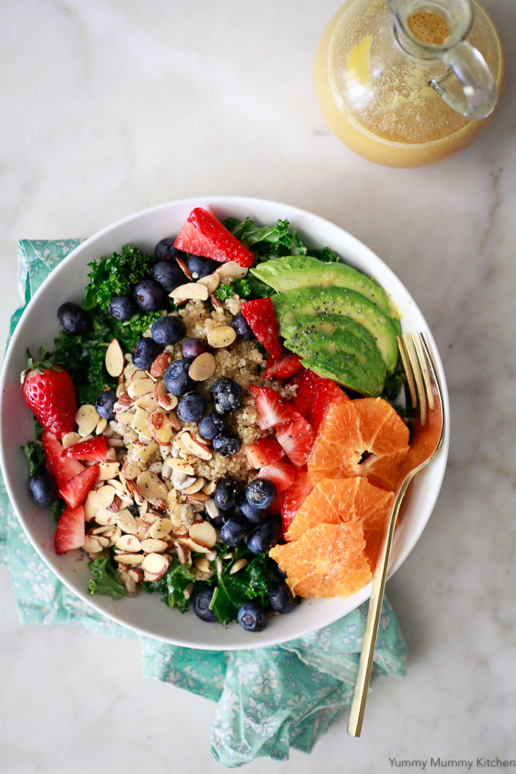 A delicious vegan kale superfood salad with blueberries, strawberries, quinoa, avocado, nuts, and seeds. This salad is served with orange vinaigrette.