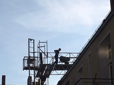 Bauarbeiter fährt Schubkarre vom Baustellenaufzug weg Richtung Dachausausbau