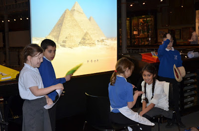 Group of pupils prepare a person for mummification with a backdrop of the pyramids on the screen behind them