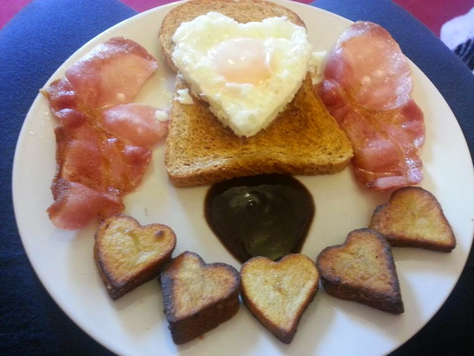 Full english breakfast, with heart-shaped egg and fried potatoes.