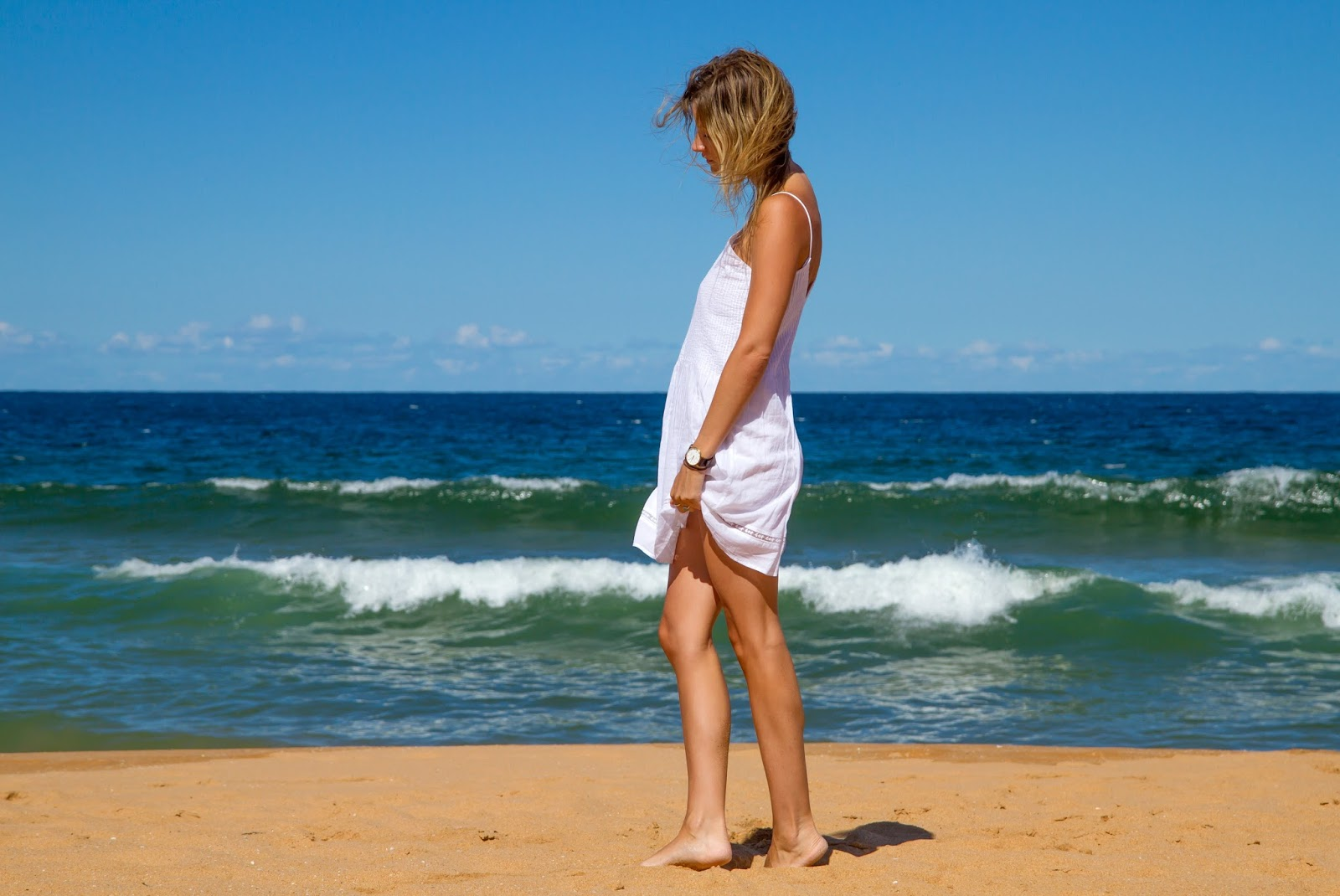 fashion and travel blogger, alison hutchinson from Styling My Life is playing in the waves at Palm Beach in Sydney, Aystralia in a white Zara sundress.