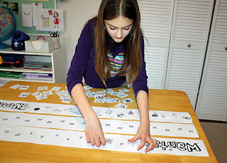 Although Tessa had completed our banner several times during the testing phase, she wanted to do it one last time...to make it official for her badge. The banner looks cooler stretched out 11 feet across the floor, but it was cold this day. We opted to divide it into three segments and work on it on the table while shutting ourselves into the school room with a space heater. We taped it all together at the end.
