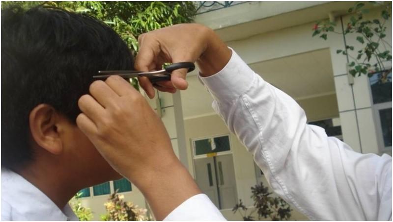 Siswa dicukur rambutnya oleh guru