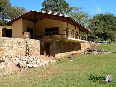 Construção com base de pedra, com pedra moledo, na construção de churrasqueira com o fogão a lenha, o forno e o forno de pizza.