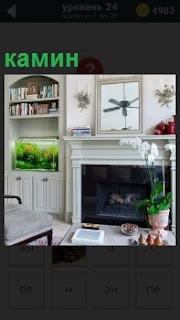 В комнате под окнами расположен камин, но не работает и рядом полка с книгами, аквариум с рыбками