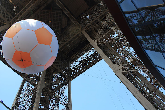Giant soccer ball hanging from the Eiffel Tower.