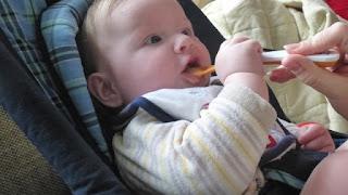 Baby bekommt Brei auf dem Löffel