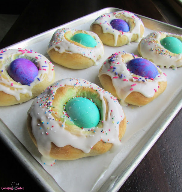 baking tray with 6 small easter breads with a hard boiled egg in the center of each