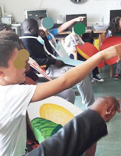Alunos sentados apontam com as mãos para participar numa atividade