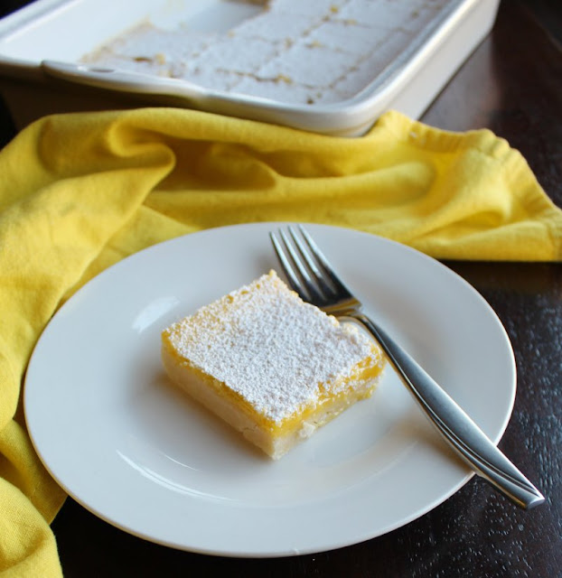 piece of powder sugar coated lemon bars on plate with fork