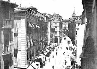 Inicio de la calle visto hacia la plaza Mayor. En las aceras se ven muchos puestos de venta con toldos.