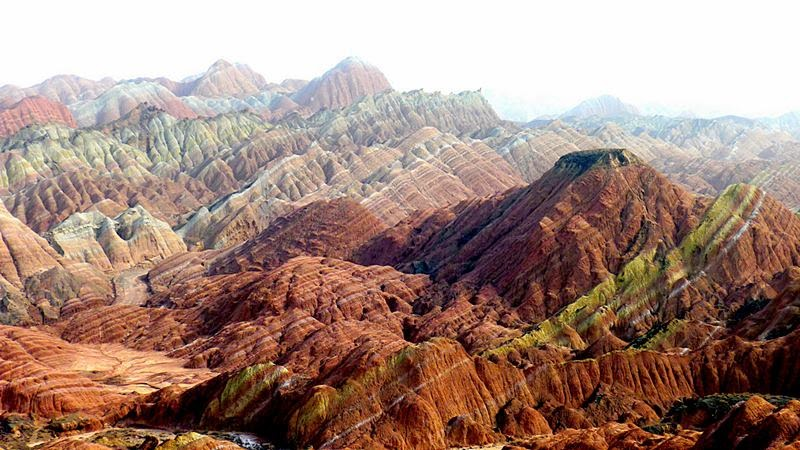 Zhangye Danxia Landform is surrounded by colorful hills, which seem to rise and fall like waves: with rock strata of different colors mixed in graceful disarray, it is an imposing and magnificent sight.