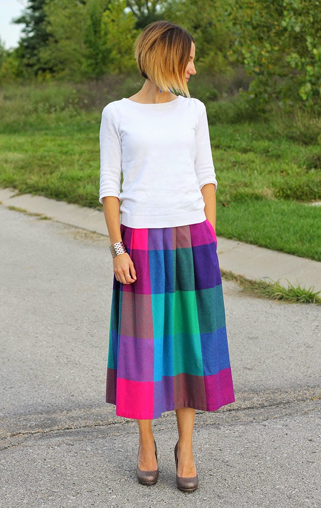 Bright plaid midi skirt, white sweater and glitter heels