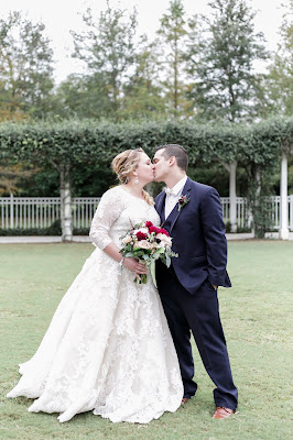 bride and groom kiss with red bouquet