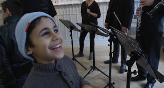 Young participant in El Sistema Söderteälje with musicians from the Royal Stockholm Philharmonic