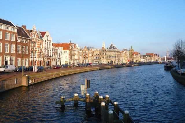 Taken from the bridge Melkbrug, this view of Haarlem, The Netherlands, along the Spaarne River shows typical Dutch architecture, the Weigh or Waag House (gray building in center), and the white tower of the Bakenesserkerk. Photo: WikiMedia.org.