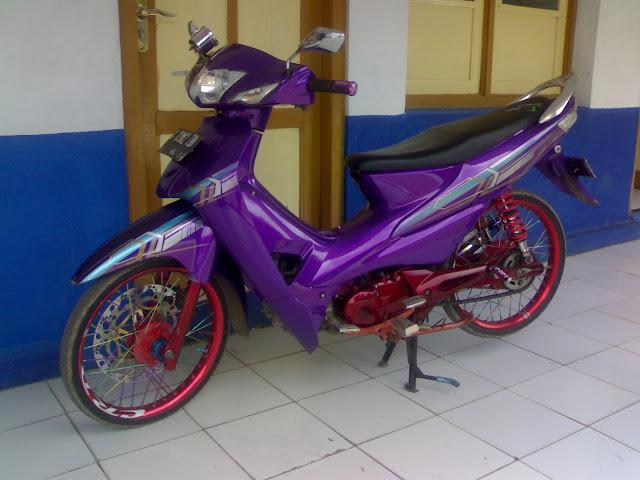 Foto Modifikasi Honda Supra  kali ini dilakukan dengan pengecatan ulang seluruh body dengan warna ungu dan merah marun serta beberapa warna striping menggunakan metode airbrush. Seluruh body dicat dasar dengan warna ungu, untuk striping diberi aksesoris paduan warna putih, abu-abu dan biru