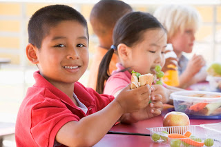 Boy eating a sandwich at school lunch table.