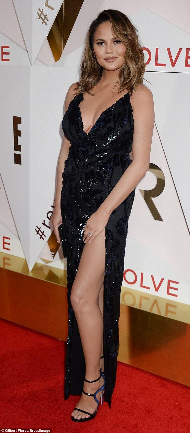 Braless Chrissy Teigen stuns in thigh high slit dress