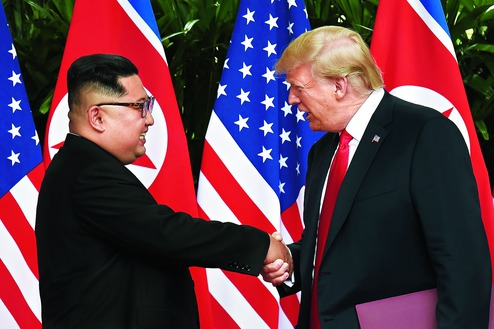 Kim Jong-un shakes hands with Donald Trump