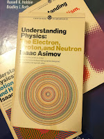 Understanding Physics: The Electron, Proton, and Neutron, by Isaac Asimov, superimposed on Intermediate Physics for Medicine and Biology.