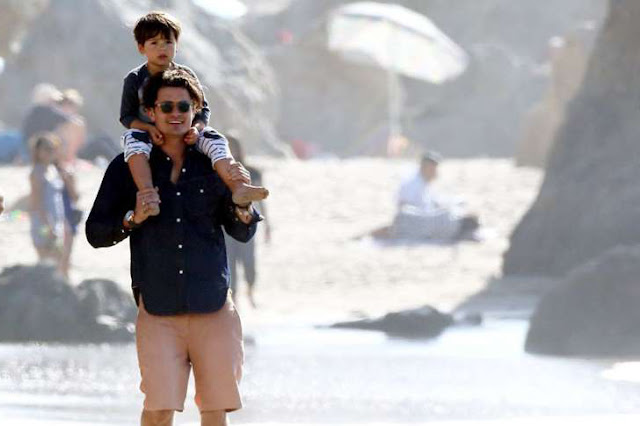 Orlando Bloom and his son taking a walk on the beach