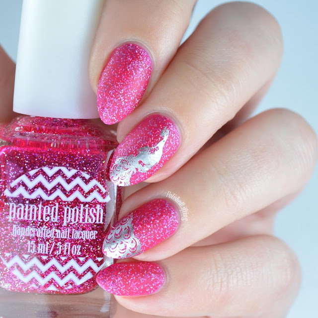 Matte pink nail polish with peacock stamping