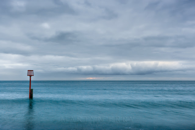 Azure ocean under a dramatic sky with red beacon on the Dorset coast
