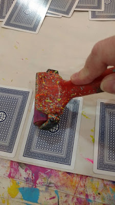 a picture of playing cards being glued down onto paper using a prayer