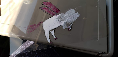 Partially erased drawing of white unicorn with pink wings, only the body is visible.  The head has been erased.