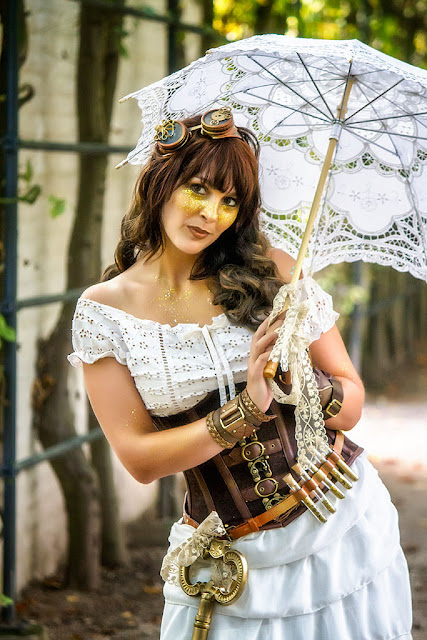 steampunk fashion cosplay gold glitter makeup, goggle, corset, parasol, skirt, and belt.