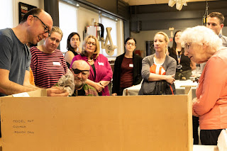 Andrew shows the group an object he is conserving in the Conservation lab