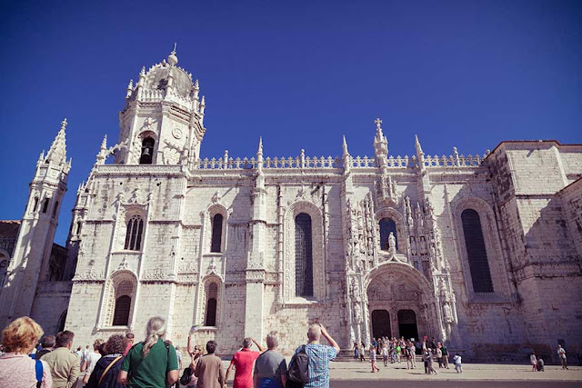 Tourists looking up at the Manualine gothic style Jeronimos Monastery in Belem, Lisbon, Portugal