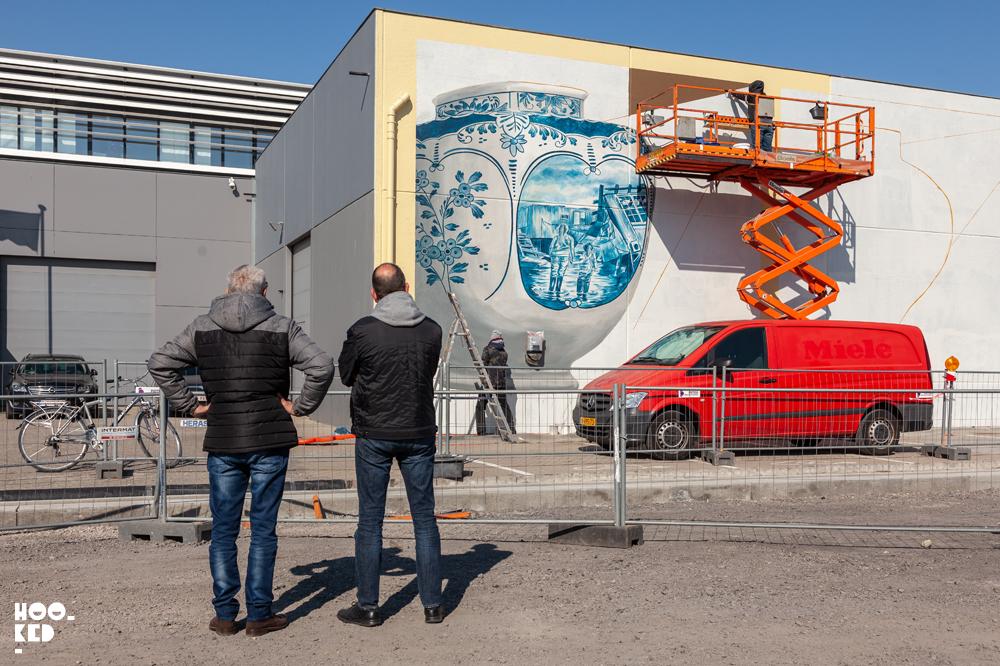 Onlookers watch artist Leon Keer at work on his 3d mural in ostend