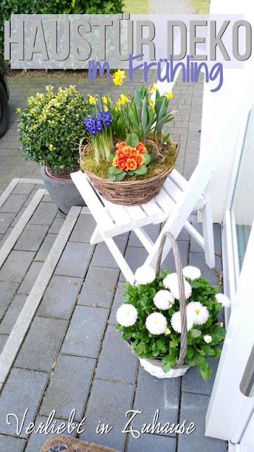 Haustür Deko im Fruehling: Blumen im Pflanzkorb stehen im Eingangsbereich