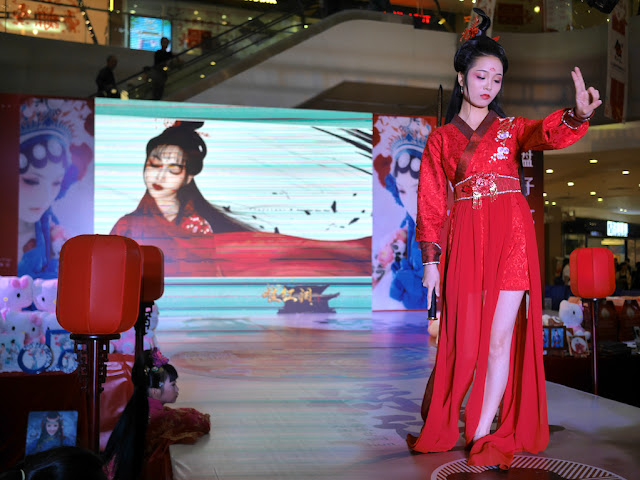female model in red traditional-style dress with only two fingers extended from her raised hand