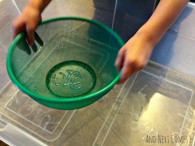 Sifting in a simple water sensory bin from And Next Comes L