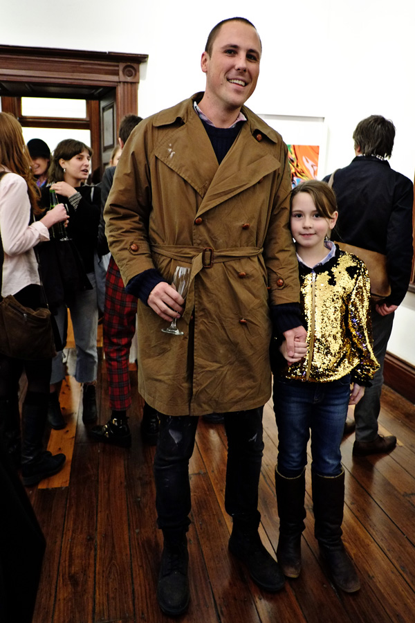 Gentleman in brown winter trench, young girl in shiny yellow gold jacket jeans and long boots at Juniper Hall. Street Fashion Sydney - Photographed by Kent Johnson.