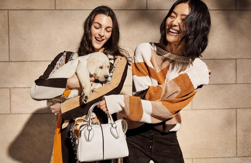 Liu Wen and Vittoria Ceretti pose with a dog on set of Tod's spring 2019 photoshoot