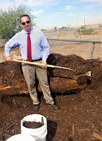 Hodgins working in the garden shoveling dirt in his office attire and sun glasses