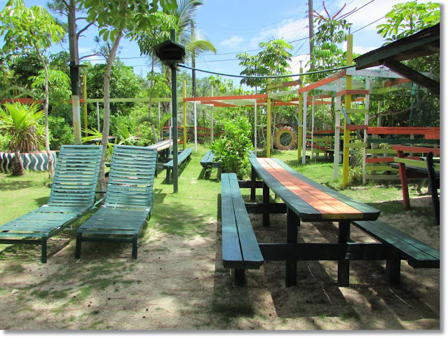 Lush island greenery surrounds picnic table and lounge chairs.