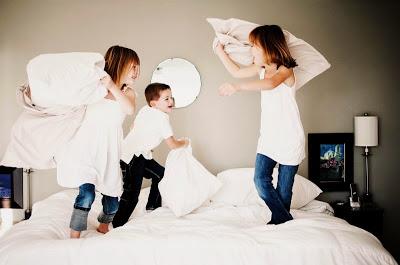 anak-anak bermain perang bantal di atas tempat tidur orang tua