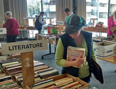 Cynthia M. Parkhill, holding a book in her right arm, looks over a sale table of other books. A sign displayed above the table of books designates their category as 'Literature.'
