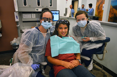 students and patient looking at the camera from clinic station.