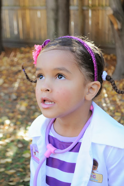 Little girl wearing stethoscope and glittery headband as Doc McStuffins