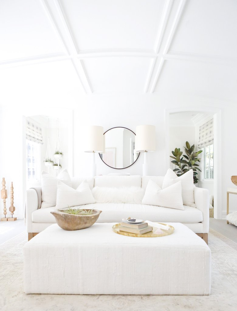 Design inspiration from this all white living space with white linen sofa, upholstered ottoman, rustic dough bowl, brass accents, and California modern farmhouse chic by Erin Fetherston. #allwhite #whitedecor #livingroom #rusticdecor