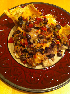Tasty plate of black bean nachos with melted cheese and home made pico salsa